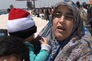 Arab woman with child in front of queue of migrants