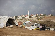 Hebron region. In the foreground, a tent where a Palestinian family lives, and in the background an illegal Israeli settlement.