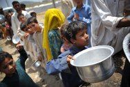 Camp for Internally displaced persons at Swabi. Children collect food distributed by Pakistan Red Crescent Society.
