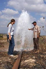 Water erupts from the newly repaired pipe, restoring life to parched fields behind the the West Bank barrier.
