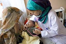 Kandahar, Afghanistan. An ICRC teaching nurse examines a child in the paediatric ward of Mirwais Hospital.