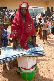 A displaced woman in Dioulabougou with her emergency items.