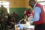 Nigerian Red Cross volunteers treating an injured villager from Ayokormor at the clinic in Warri.