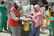 A Pakistan Red Crescent volunteer distributes food and hygiene items to flood-affected families at Jumu Agham in Larkana district, Sindh.
