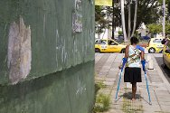 Colombia, Cali. A mine victim walks with crutches.