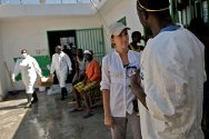 In front of dispensary at the civilian prison in Port-au-Prince, an ICRC delegate talks to a detainee working in the cholera-prevention programme. In the background, oral rehydration salts are being delivered.