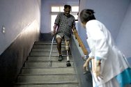 India, Jammu. Physical rehabilition centre run by the Indian Red Cross with ICRC support. A man walks down the stairs in front of the technician who will adjust his artificial leg.