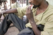 Masvingo Remand Prison, Masvingo, Zimbabwe.  A malnourished prisoner eating a plumpy nut, a rich therapeutic food.