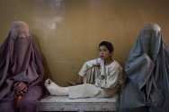 Mirwais Hospital, Kandahar. A boy who broke his leg while running from the scene of a shooting waits with his mother.
