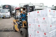 Red Cross staff load the packages onto trucks for distribution to flood victims.
