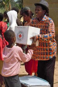 Côte d'Ivoire. A Red Cross worker hands over a box of emergency supplies to a boy displaced by the fighting.