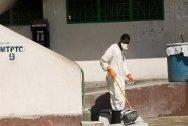 Port au Prince civilian prison. Dressed in protective clothing, a prisoner disinfects the prison's cholera treatment centre.