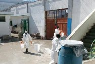 Civilian prison, Port-au-Prince. Wearing masks, rubber boots and protective clothing, prisoners ensure that hygiene is maintained in the prison's cholera treatment centre.