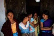Displaced women from the Rabha community wait for support from the Red Cross in a local school.
