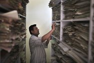 Al-Zubair Centre, Basra. A staff member searches through files on missing persons.