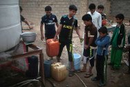 Sadr City, Baghdad, Iraq. Residents fill containers with clean drinking water provided by an ICRC project.