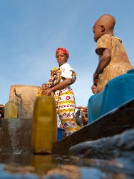 DRC, Nord-Kivu, Kibirizi. A woman collects drinking water from a supply point built by the ICRC.