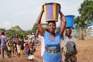 Nimba County, Liberia. Rosine (in the blue shirt) carries water distributed by the Buutuo Branch of the Liberian Red Cross. A water purification and distribution unit provides 75,000 litres of water per day to more than 10,000 people, both refugees and their Liberian hosts.