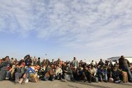 People fleeing the violence in Libya wait for transportation at the Libya and Tunisian border crossing of Ras Jdir.