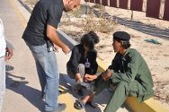 Brega, Libya. ICRC delegates provide first aid to a fighter wounded by a bullet.