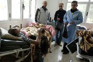 Al Bayda Hospital. A patient with a gunshot wound receives a visit from his family.