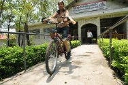 Tulasi riding a bicycle at the Green Pastures Hospital and Rehabilitation Centre.