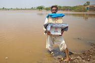 Pakistan. Mohammad Saleem returns to his damaged house across a flooded field, carrying a cooking set, blanket and mosquito nets. His village was hit hard by the monsoon that started on 9 August 2011.