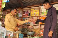 Ghanchattar, Pakistan-administered Kashmir. Manshad Ahmed serves a customer in the shop he started with ICRC support.