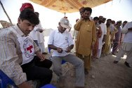Alahabad village, Taluka Garhi Khero, Jacobabad district, Sindh province, Pakistan. ICRC and Pakistan Red Crescent Society staff check beneficiaries' tokens before distributing rice seed, fertilizer and tools.