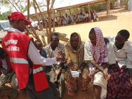 One of the four refugee camps in Dadaab, Kenya. A KRCS volunteer helps a refugee make a phone call to a relative.