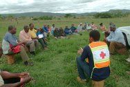 Hhohho region, Swaziland. Baphalali Swaziland Red Cross Society volunteer Nhlanhla Mathunjwa talks to community leaders of Mkhuzweni.