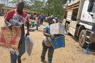Côte d'Ivoire. An ICRC employee helps carry one of the household kits distributed to IDPs.