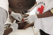 Headquarters of the Red Cross of Côte d'Ivoire, Plateau. First-aiders from the National Society insert stitches in the scalp of a person injured in the fighting.