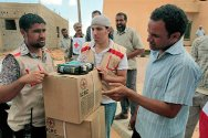 Washka, 100 km west of Sirte, Libya. Libyan Red Crescent volunteers prepare supplies for distribution.