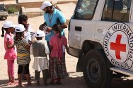 Zintan, Libya. ICRC staff explain the risk from unexploded munitions to a group of children.