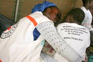 Senegal. RFL activities at the Grand Magal, Touba, 2011. A volunteer reassures a child separated from her parents.
