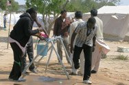 Choucha Camp, Tunisia. The men of the camp fill their buckets at a tapstand.
