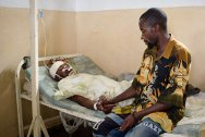 DR Congo. Bethesda hospital in Goma, North Kivu province. A man cares for his brother suffering from a gunshot wound. The two brothers were riding their motorcycle taxi when they were attacked.
