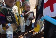 Ndélé. Children receiving water trucked in by the ICRC to the camp situated around the Mission for the Consolidation of Peace in the Central African Republic.