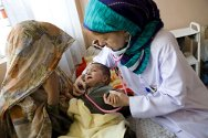Kandahar, Afghanistan. An ICRC teaching nurse examines a child in the paediatric ward of Mirwais Hospital.