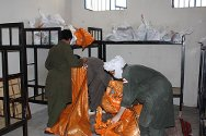 Afghanistan. Detainees' bedding and clothes are packed into large bags and taken out into the prison courtyard before the cells are cleaned to rid them of scabies mites. Books and personal possessions are packed separately and stored safely.
