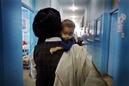 Mirwais hospital, Kandahar. A father carries his son in the therapeutic feeding centre supported and run by the ICRC.