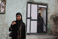Malika (foreground) and Hamida outside Hamida's house.  Both women have lived in Qoliobchakan for years.