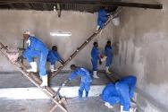 Uvira Central Prison, South Kivu, DRC. Workers treat the walls of the mens' cells with lime.