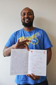 Muxammad Diiriye shows off the Red Cross message he received from his family.