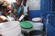 Cité Soleil residents fetch water at a fountain restored by the ICRC.