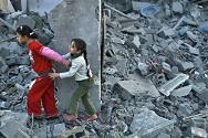 Palestinian girls run away after an Israeli air strike on a house in the northern Gaza Strip.