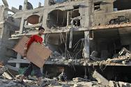 A Palestinian carries his belongings from a destroyed house after an Israeli air strike in the northern Gaza Strip.