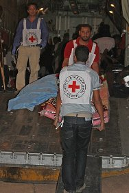 Al Kufra Airport, Libya. ICRC staff lift a casualty onto an aircraft bound for Tripoli, where he will receive hospital treatment.