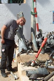 Libya. An explosive ordnance disposal team leader checks a display of unexploded ordnance for dangerous items.